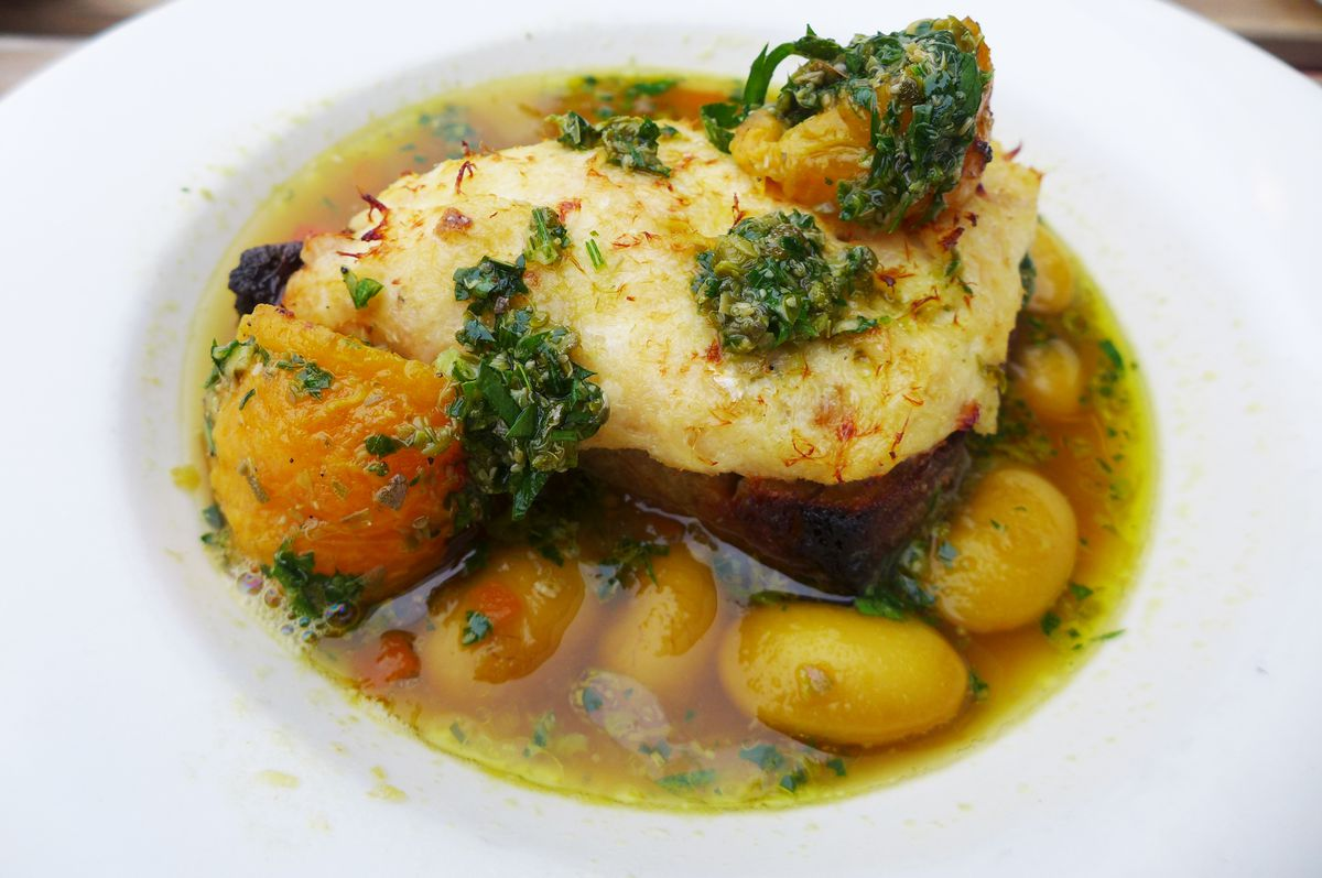 A white fish filet in broth surrounded by giant beans.