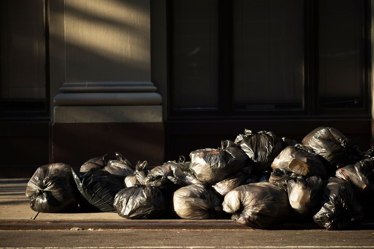 Black trash bags lie in the street in front of a dark building. The image is used to illustrate New York City's precarious budget situation, after the coronavirus pandemic has caused many cuts to trash collection.