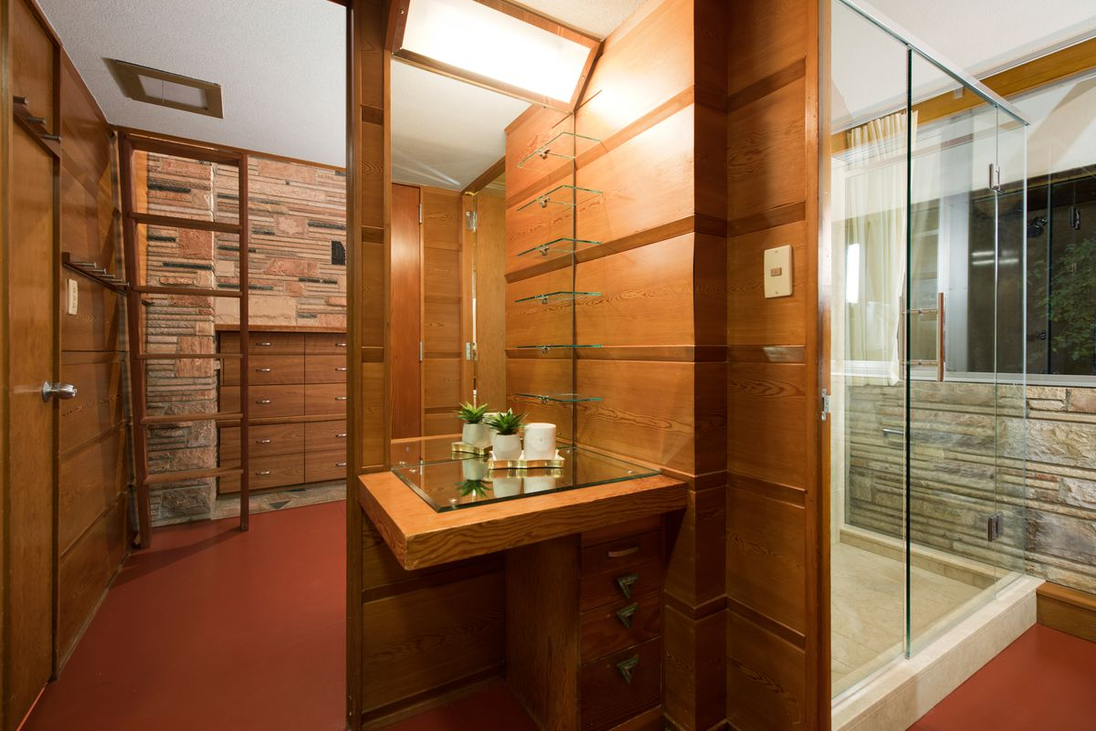 A vanity in the bathroom sits on the opposite side of a large step-in shower.