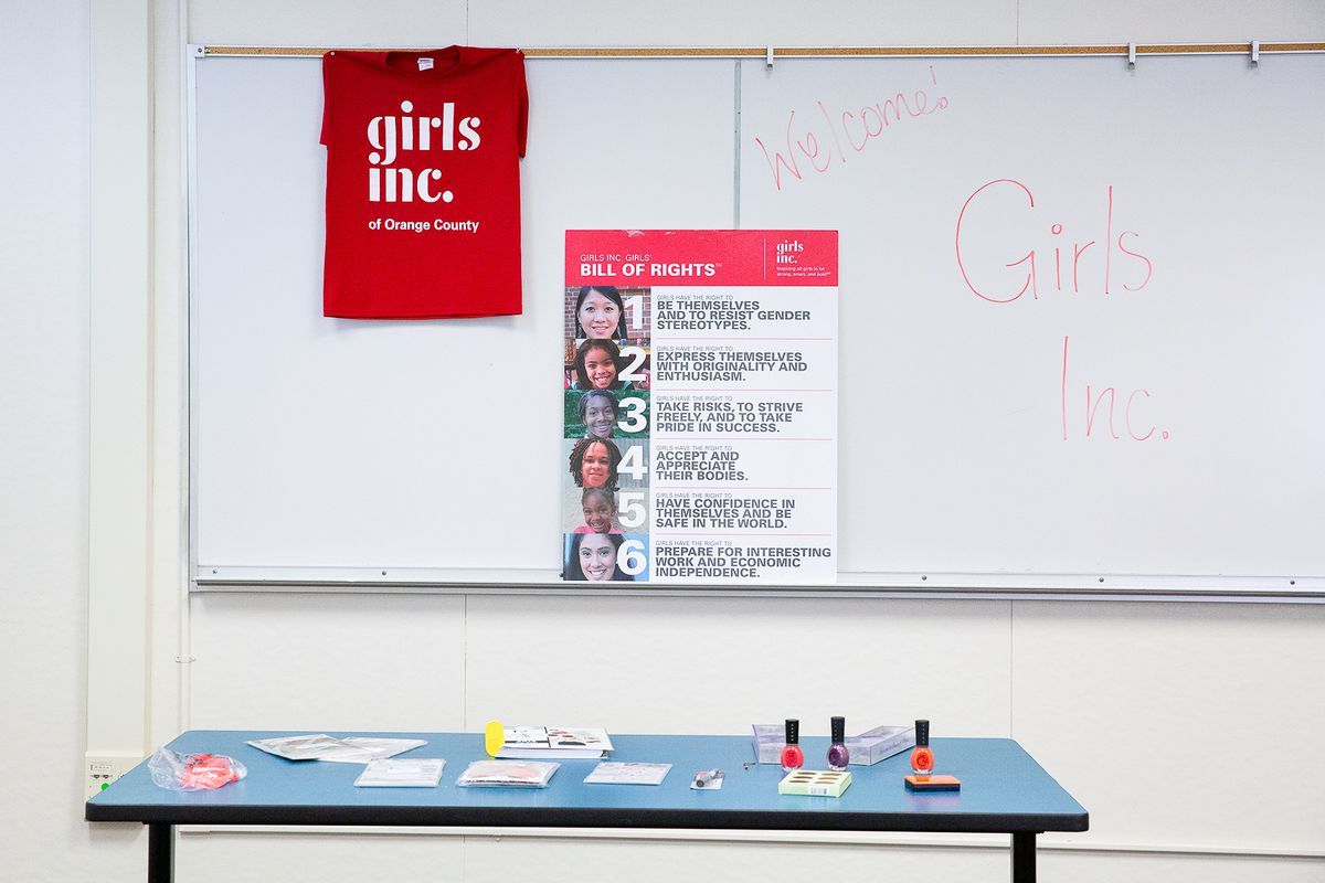 "A ""Girls' Bill of Rights"" is posted on a classroom, behind a table holding nail polish and other prizes."