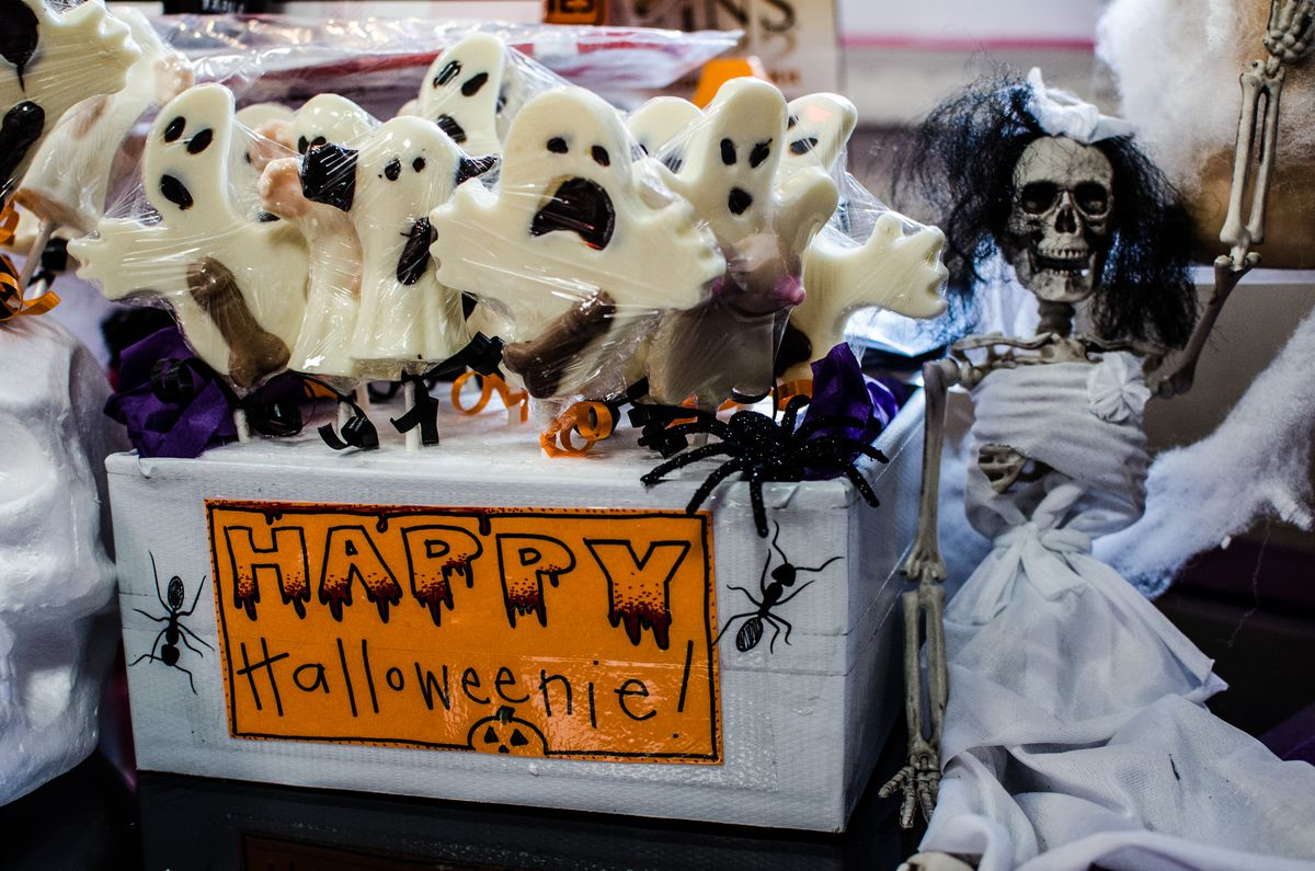 """At an adult bakery, ghost-shaped chocolates with penises are wrapped in plastic, with a sign that says """"happy Halloweenie"""""""