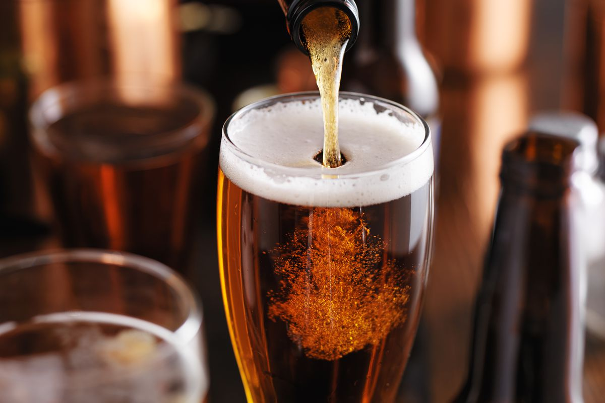 A dark amber beer gets poured from bottle to glass.