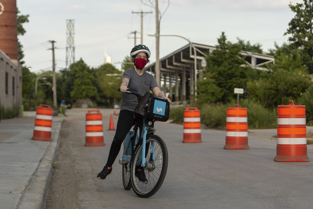 Alex Raynor, 29, lets her feet off the ground while her bike coasts along so that she can learn how to balance with it during a learn to ride a bike class with CDOT in the East Garfield Park Neighborhood, Thursday, July 16, 2020. | Tyler LaRiviere/Sun-Times