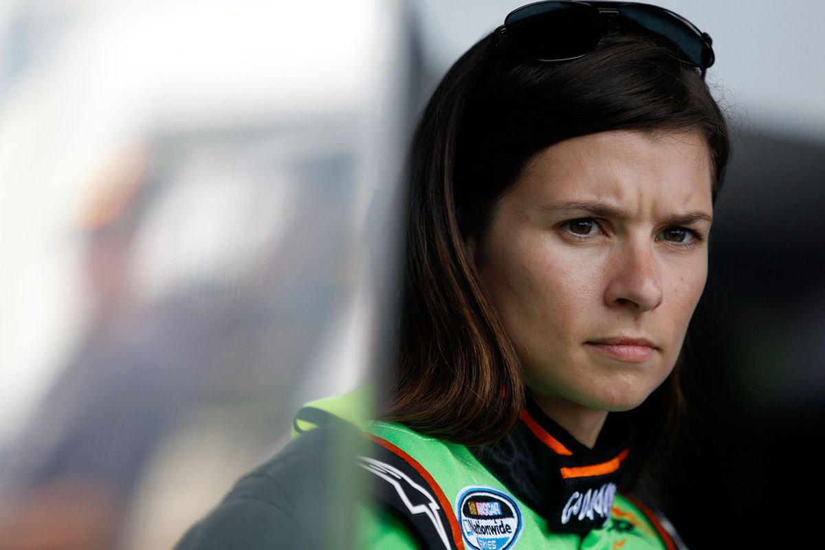 Danica Patrick looks on in the garage during practice for the NASCAR Nationwide Series Subway Jalapeno 250 at Daytona International Speedway.