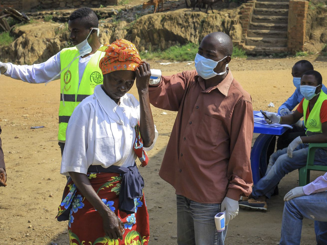 People crossing the border from Eastern Congo into Uganda have their temperature taken to check for symptoms of Ebola on June 12, 2019.