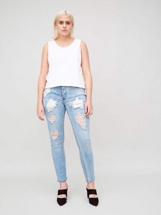 A model in distresses light blue skinny jeans.