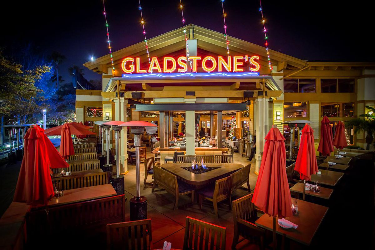 Outdoor patio set with tables and umbrellas in front of the entrance of Gladstone's in Long Beach.