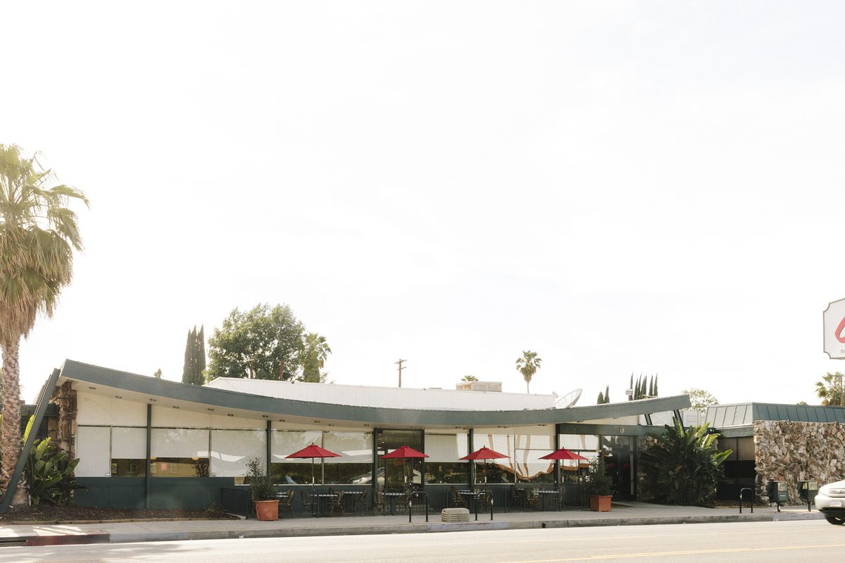 """A single-story midcentury diner with a swooping long roof and a neon sign of the restaurant's name (""""Corky's)."""