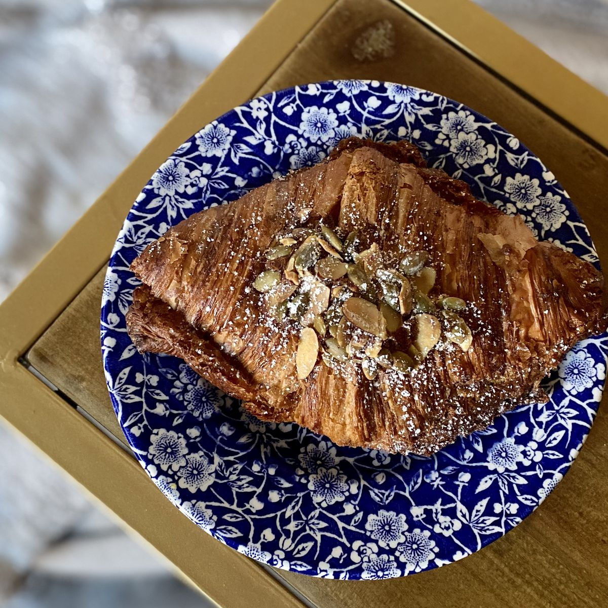 A croissant topped with almonds and pepitas on a blue-flowered plate.