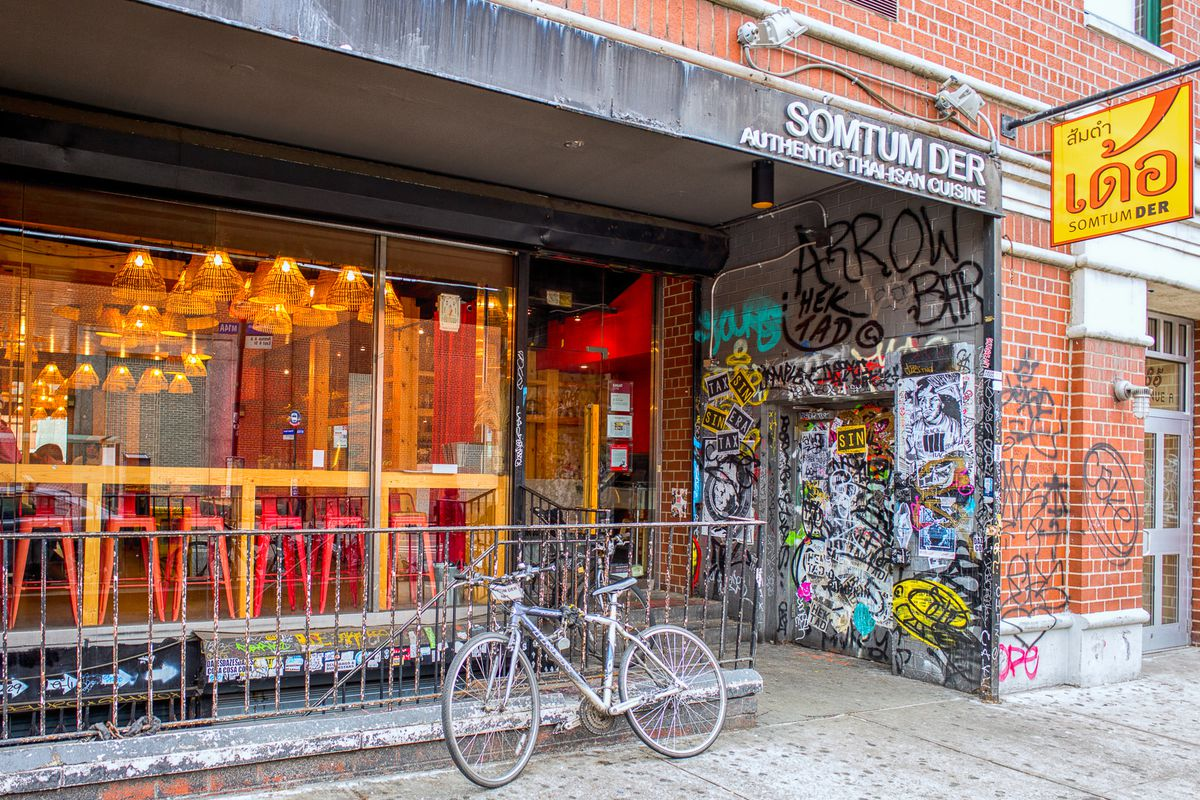 The exterior of the East Village restaurant Somtum Der with bright yellow lights and red stools that can be seen in the front