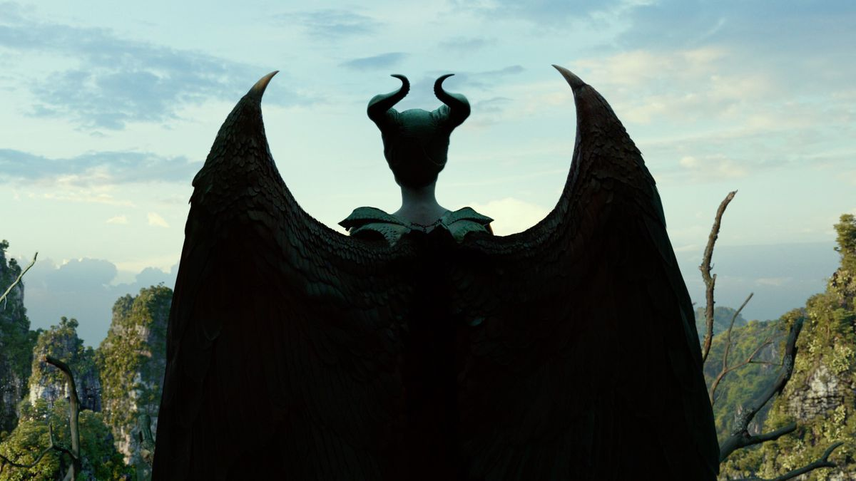 maleficent stands with her winged back turned to camera