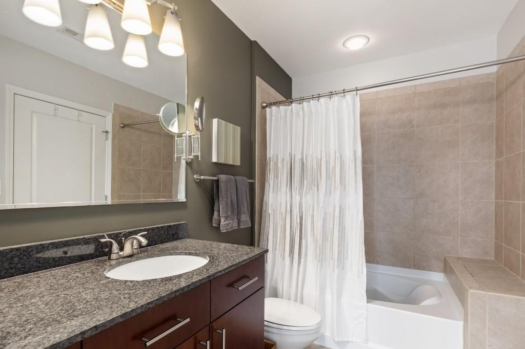 A bathroom with a gray sink and beige tiled tub area.