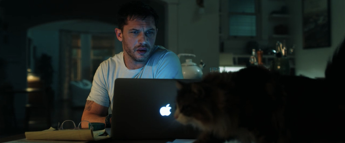 Eddie sits in front of his laptop. A furry cat is in the foreground. It is Mister Belvedere.