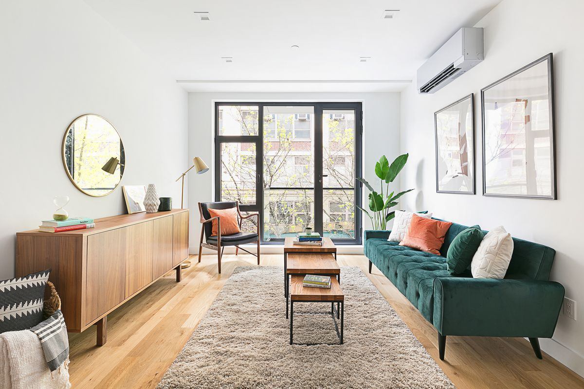 A living room with a brown rug, a green couch, wooden furniture, a planter, and a door that leads to a balcony.
