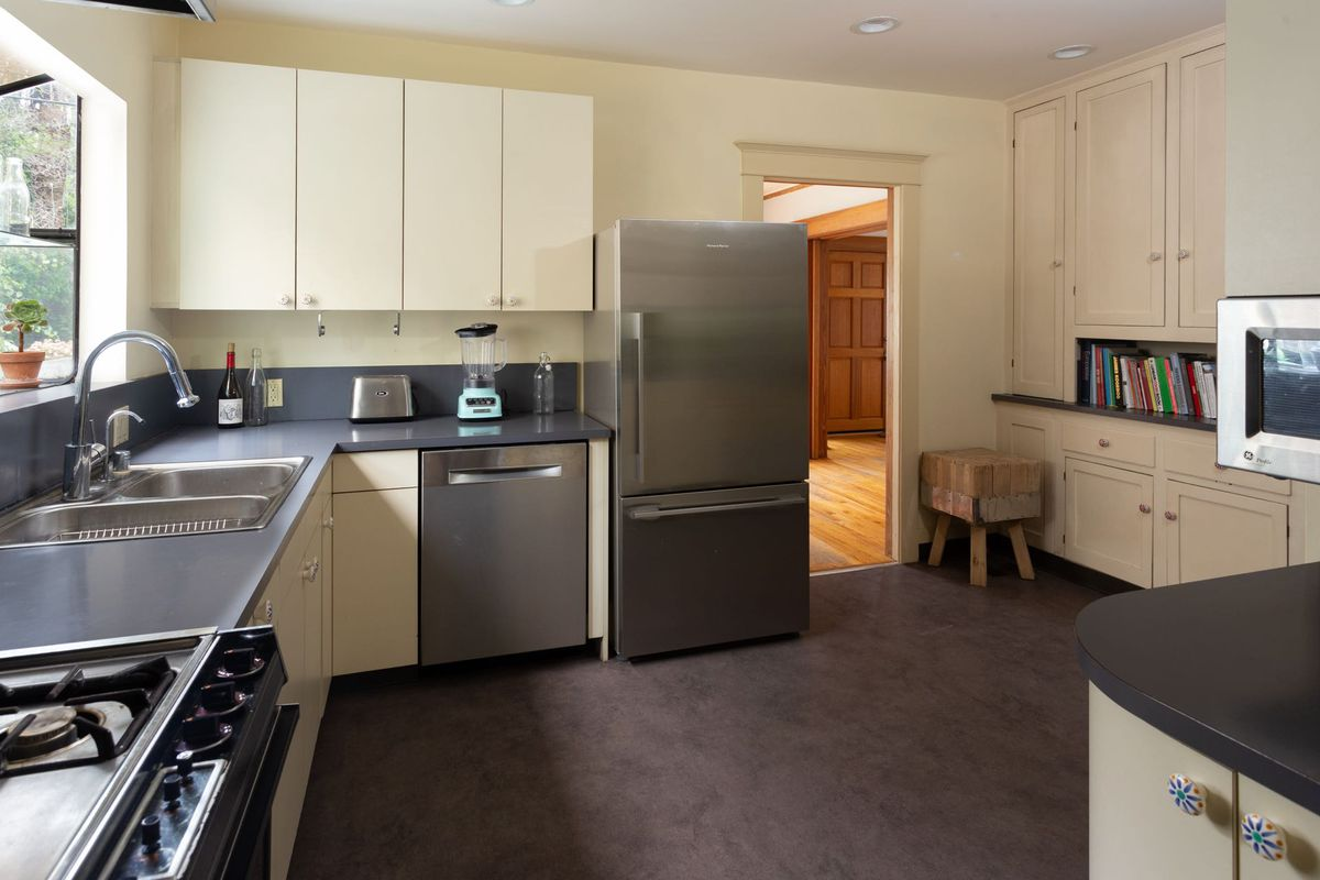 A kitchen with gray counters, stainless steel appliances, and dark gray floors.