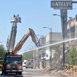 Chicago firefighters work at the scene after a three-alarm fire broke out about 3:30 a.m. and destroyed the mostly vacant, 3-story Gatelys People's department store at 112th Street and Edbrooke Avenue, June 7, 2019.