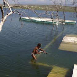 In this Sept. 5, 2012 photo, a man stands on the wall of a submerged home to fish in Lake Azuei near Jimani, Dominican Republic, on the border with Haiti. The waters' rise has worsened exponentially in recent years, especially after heavy rains in 2007 and 2008 hit the island of Hispaniola. Tropical Storm Isaac dumped more water on the region last month, sparking more damage.