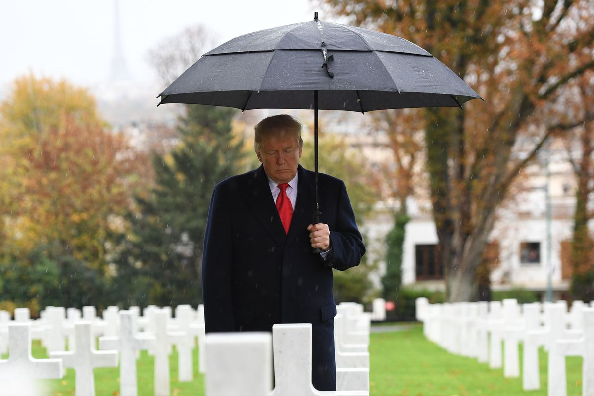 Donald Trump holding an umbrella while standing looking at a line of grave markers.