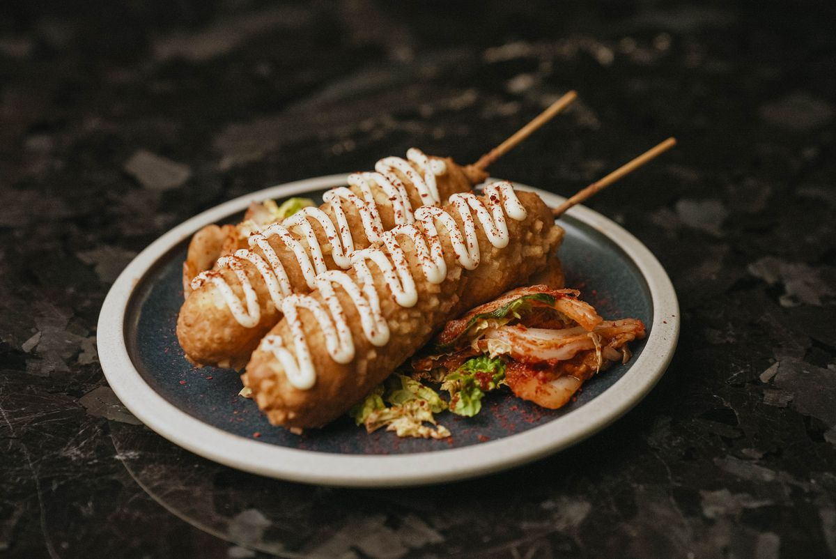 Two corndogs sit on a plate, each topped with a zigzag of a white sauce. They sit on a bed of kimchi. The plate sits on a dark marble surface.