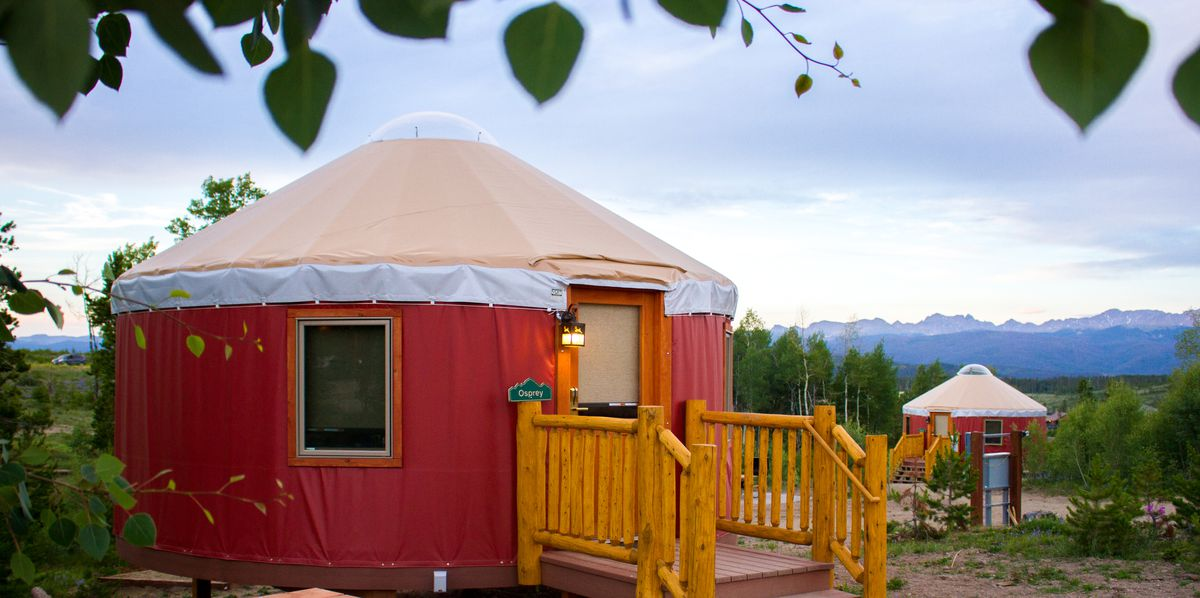 The exterior of a yurt in Colorado. The facade is red with a tan and white roof. There are mountains in the distance.