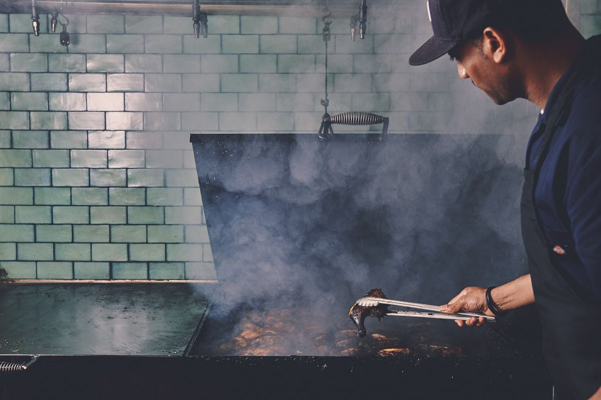 Junior Felix smokes chicken at Glady's Jerk Center