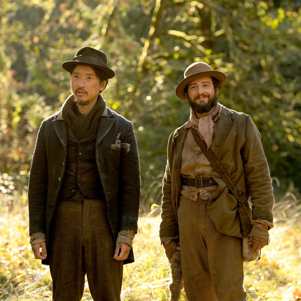 John Magaro and Orion Lee wearing frumpy brown coats in First Cow