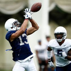 BYU wide receiver Micah Simon (13) catches the ball in front of safety Dayan Ghanwoloku during the Cougars' practice in the Indoor Practice Facility on Thursday, March 15, 2018, in Provo.