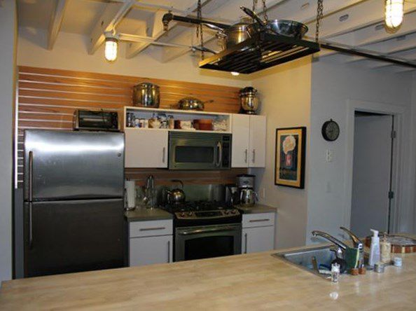 The view of a kitchen and its counter and cabinetry over another counter.