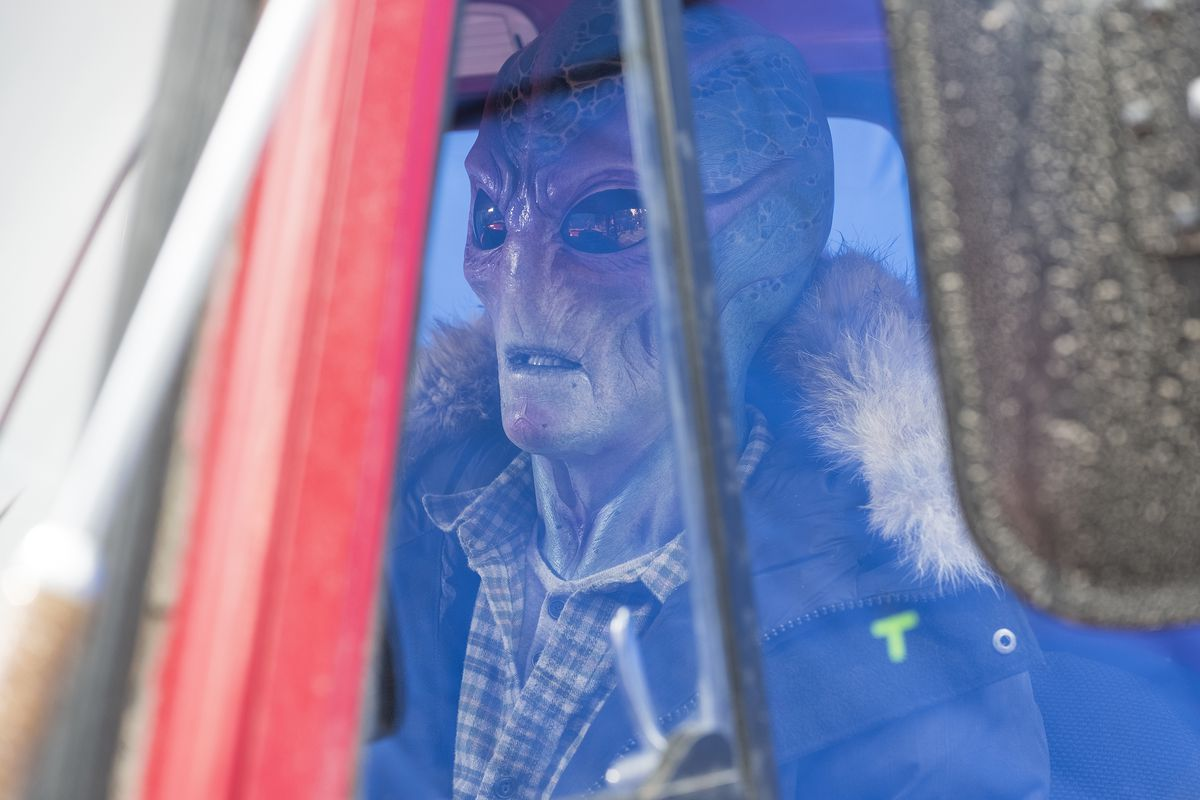 Alien Harry sits in his pickup truck in Resident Alien.