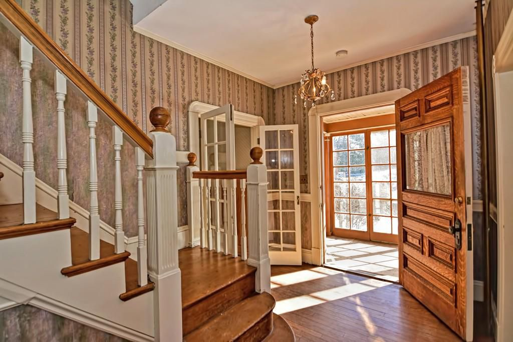 The bottom of a staircase, with a large door opening into a sunroom.