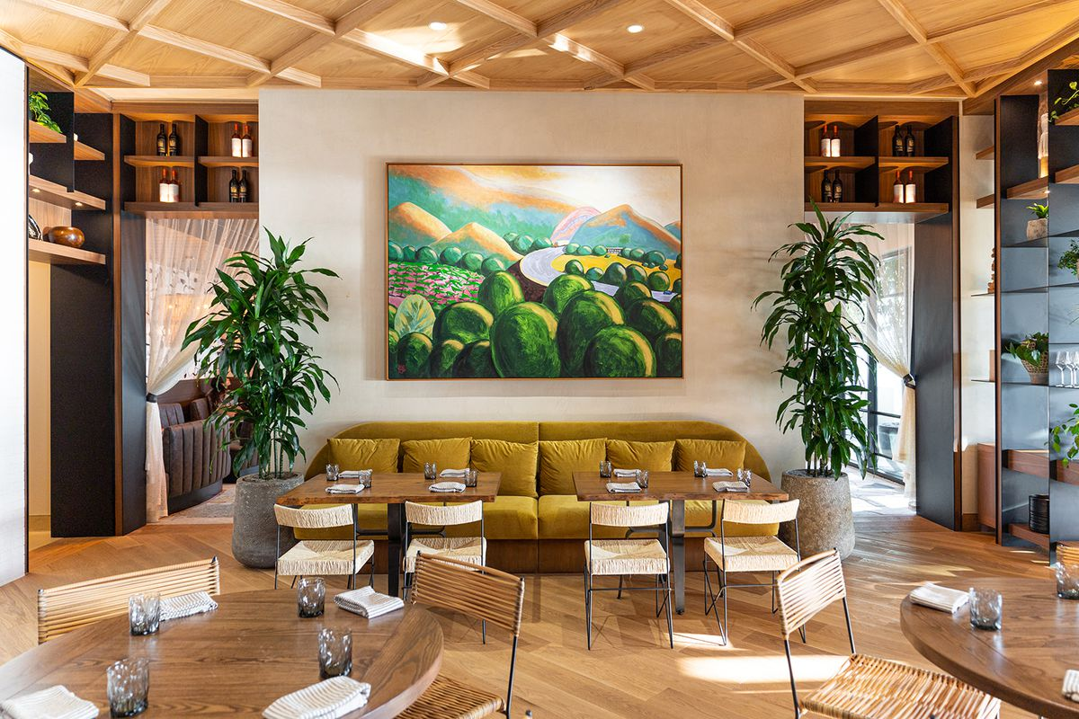 A colorful painting of the Valle de Guadalupe hangs above dining tables at Valle restaurant.