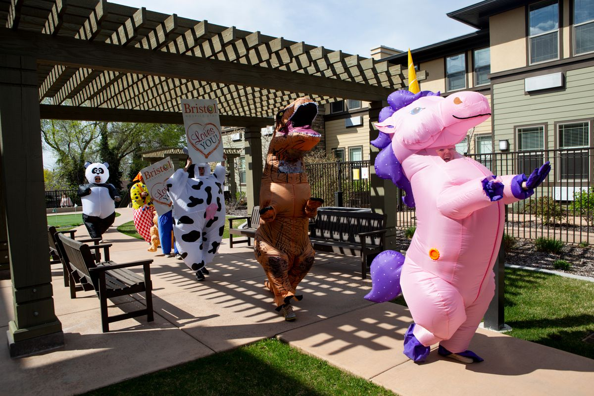 Brittany Russell, director of marketing at The Ridge Cottonwoord, helps lead a parade of Bristol Hospice Utah volunteers while wearing an inflatable unicorn suit outside of Spring Gardens Assisted Living in Holladay on Saturday, April 18, 2020.