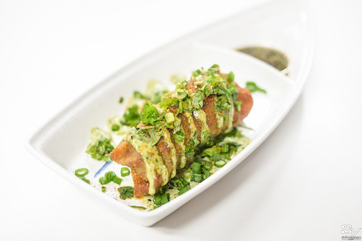 Phorale's chimichinos, spicy pork egg rolls with avocado crema and salsa verde, on a white plate against a white background.