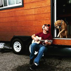 Ivor plays guitar beside Morti. The two live in a tiny house named Tad Cooper.