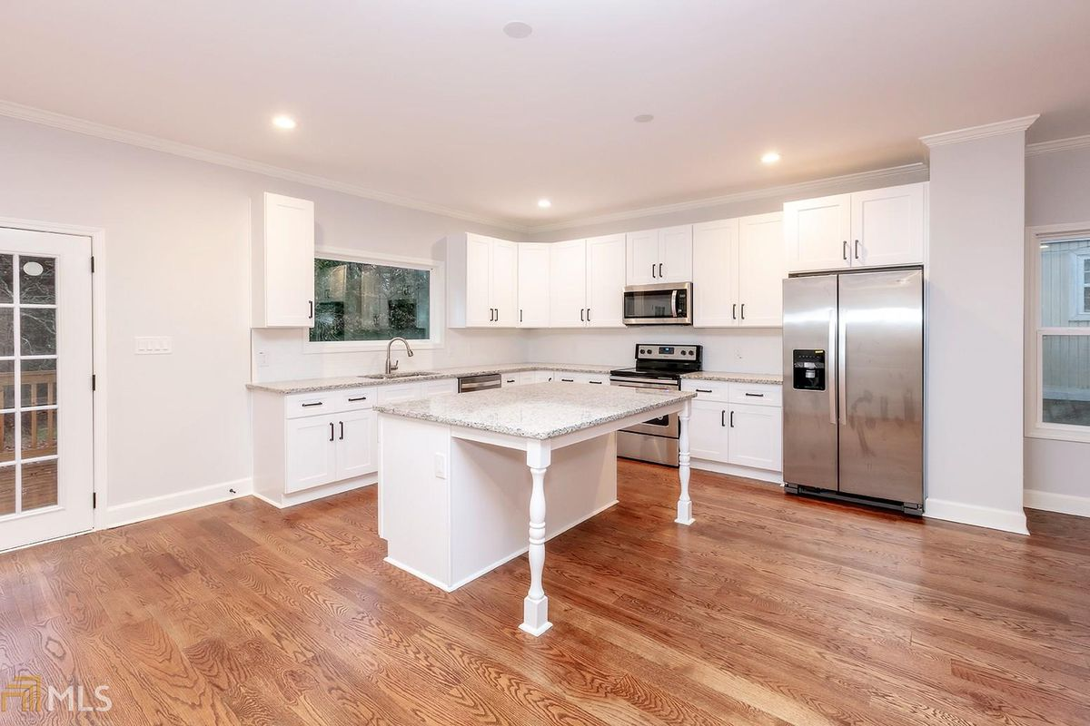 Kitchen with white cabinets and island and stainless appliances.