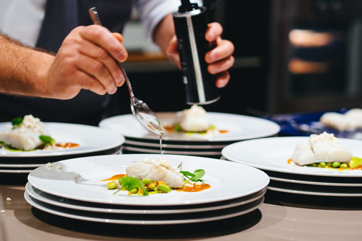 chef plating dishes with fork in hand