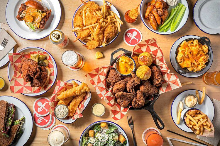 A variety of fried chicken, sides, and beverages spread out on a table.