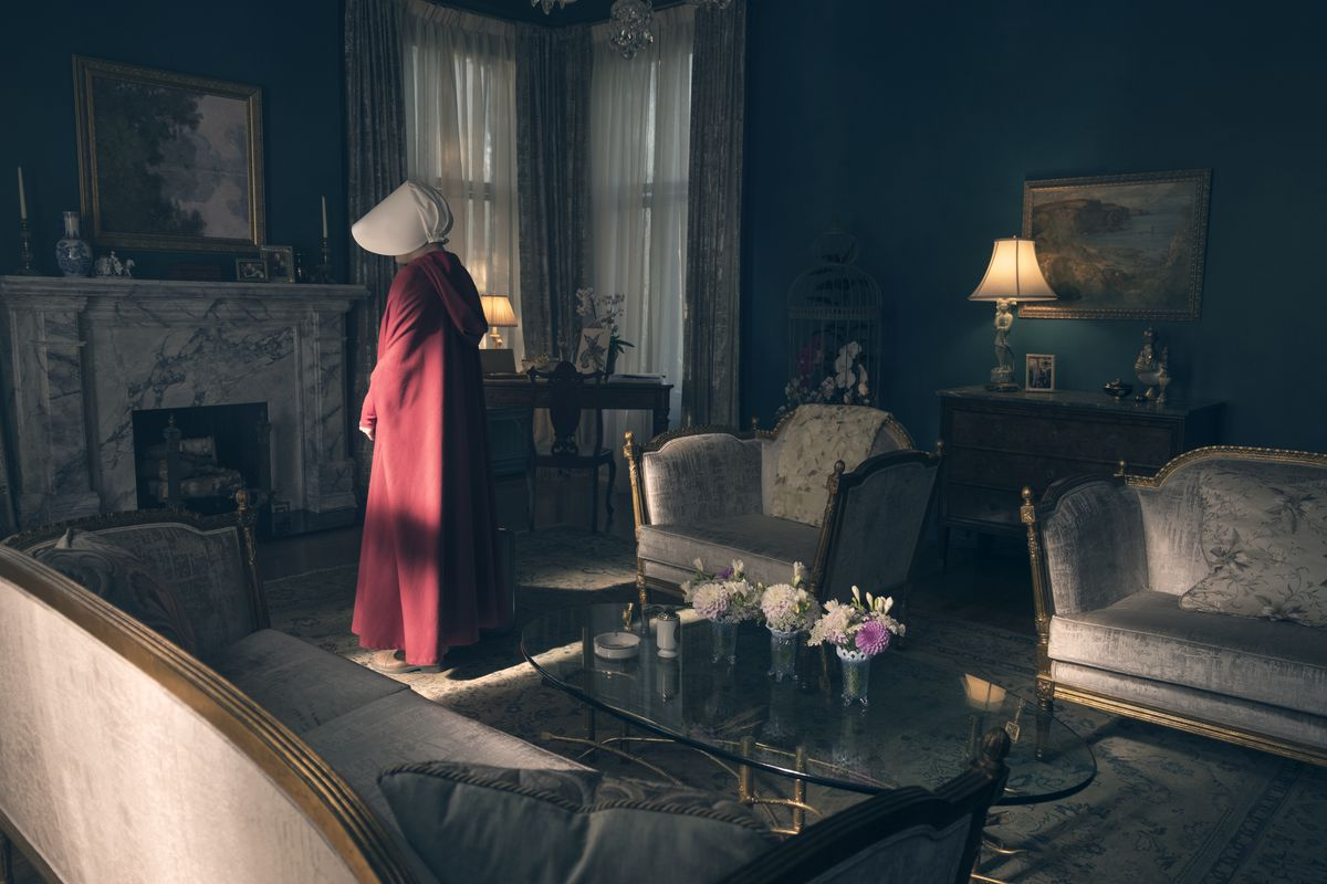 A rich interior of a home in the television series A Handmaid's Tale, featuring white marble, rich green colors, and low light.