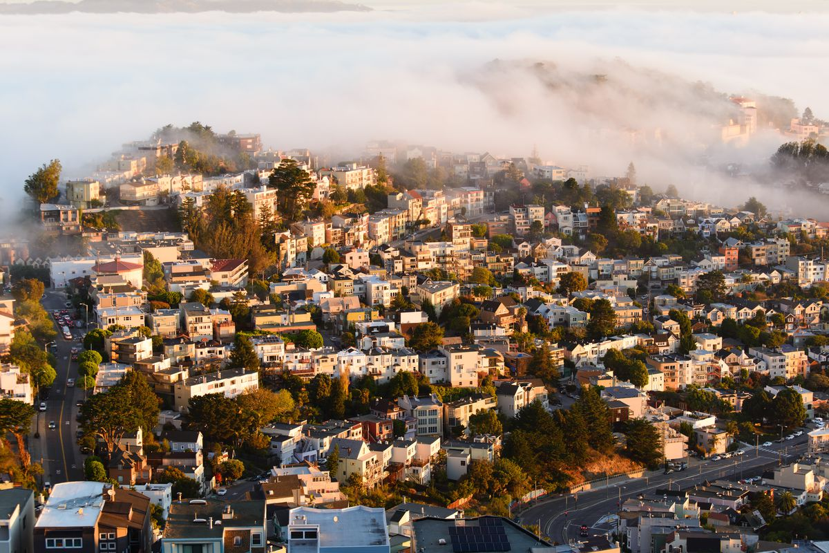 homes in SF shrouded in fog on a hill.