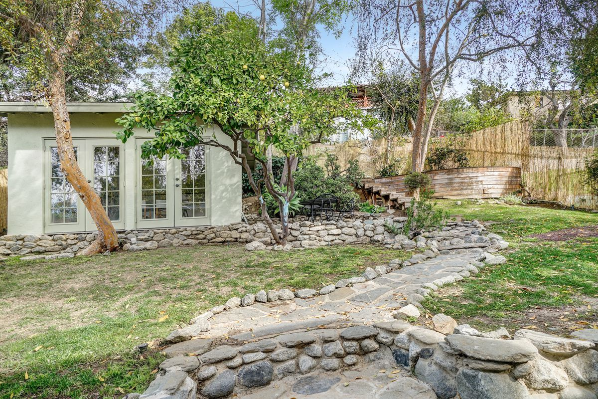 An enclosed yard with a stone wall and pathways marked with stones