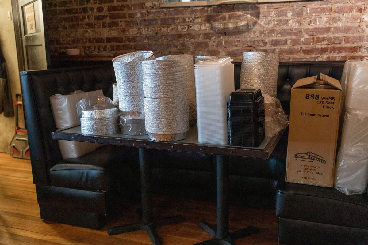 To-go supplies and containers stacked on top of dining room tables at St. Roch