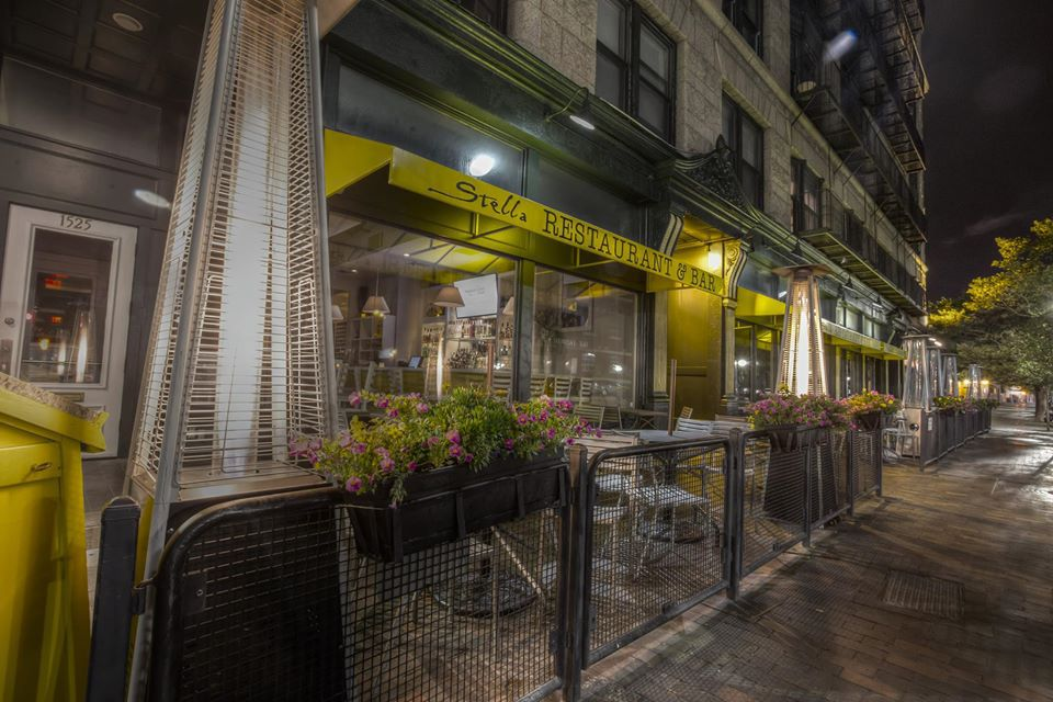 Nighttime exterior view of a restaurant called Stella, with a yellow awning and small sidewalk patio area