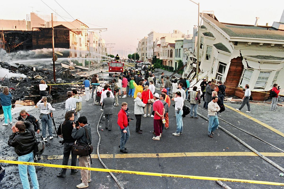 Firefighters extinguish fire in the Marina District following the 1989 quake. Buildings have crumbled into the streets. People are walking in the streets dazed. Emergency tape blocks off part of the street.