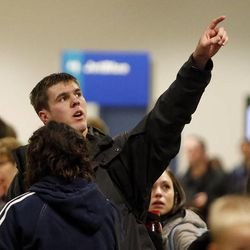 Glenn Mackay points to a monitor at Salt Lake City International Airport  as flights were delayed or canceled during a snowstorm, Thursday, Dec. 19, 2013. He is hoping to get to his fianc's home in San Antonio.