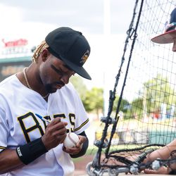 Salt Lake Bees' Jo Adell signs a ball for a fan at Smith's Ballpark in Salt Lake City.