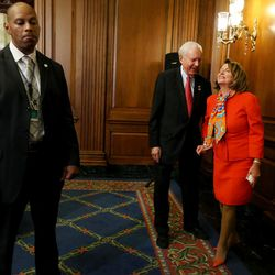 A Secret Service agent stands by as Sen. Orrin Hatch, R-Utah, president pro tem of the U.S. Senate and member and former chairman of the Senate Judiciary Committee, confers with House Democratic Leader Nancy Pelosi, D-CA, after a bipartisan, bicameral enrollment ceremony for the Every Student Succeeds Act (S. 1177) at the Capitol in Washington, D.C., on Wednesday, Dec. 9, 2015. The Secret Service has been protecting the senator due to his status as president pro tem.