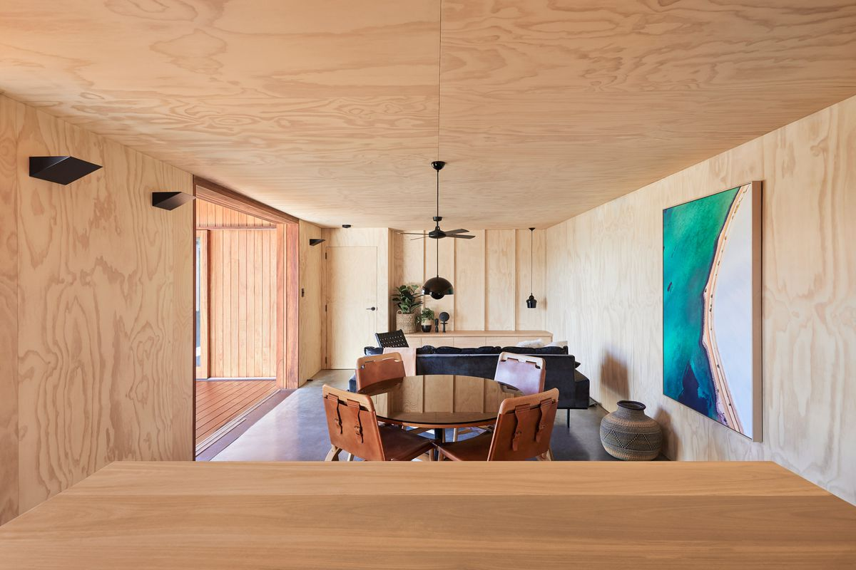 The living room features plywood walls throughout, a black sofa in the distance, a small round dining table with four chairs in the foreground. A cerulean and white artwork hangs on the right wall.