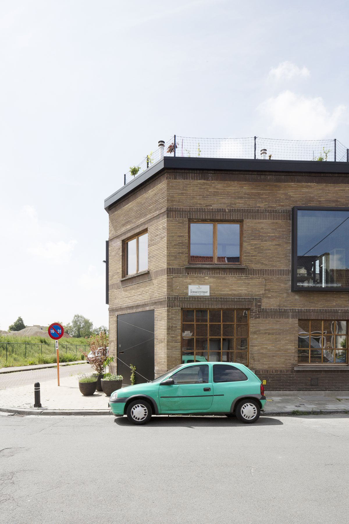The exterior of a house. The facade is brown brick and there is a bright green car sitting outside of the building. There are multiple windows.