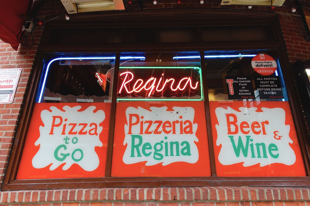 "Front window of Pizzeria Regina's original North End location, featuring red, green, and white signage that reads ""pizza to go,"" ""Pizzeria Regina,"" and ""beer and wine,"" along with a red and green neon sign that says ""Regina"""
