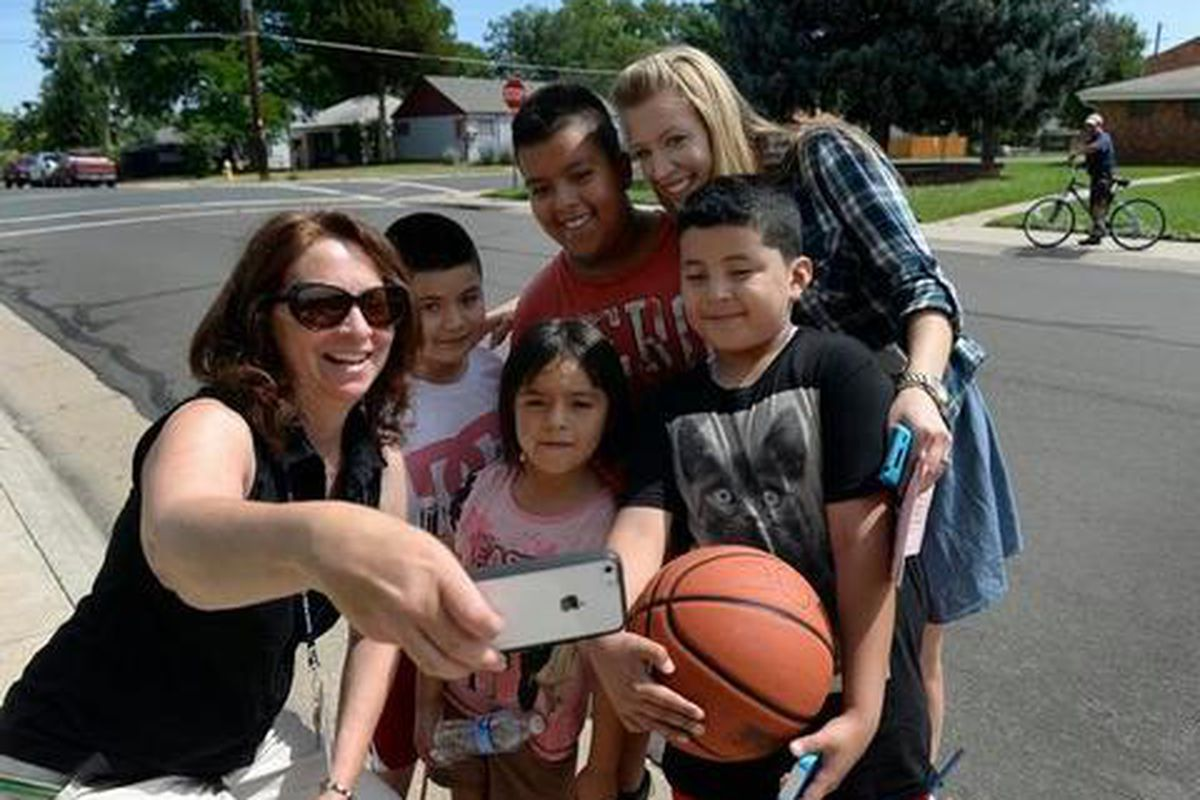 Kindergarten teacher Lori Manhart, left, and school psychologist Jennifer Keller Johnson take a selfie with students in 2014. Home visits are a good way for educators to build relationships with kids, the report found.